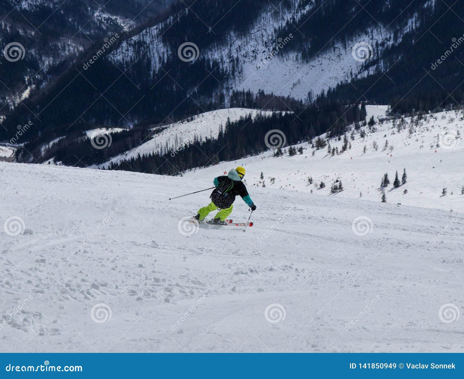 Mannelijke skiër die bergaf ski?en Jongen die neer op skis dalen Snijd positie Atleticcijfer Gele helm Zwarte rugzak gevaarlijk