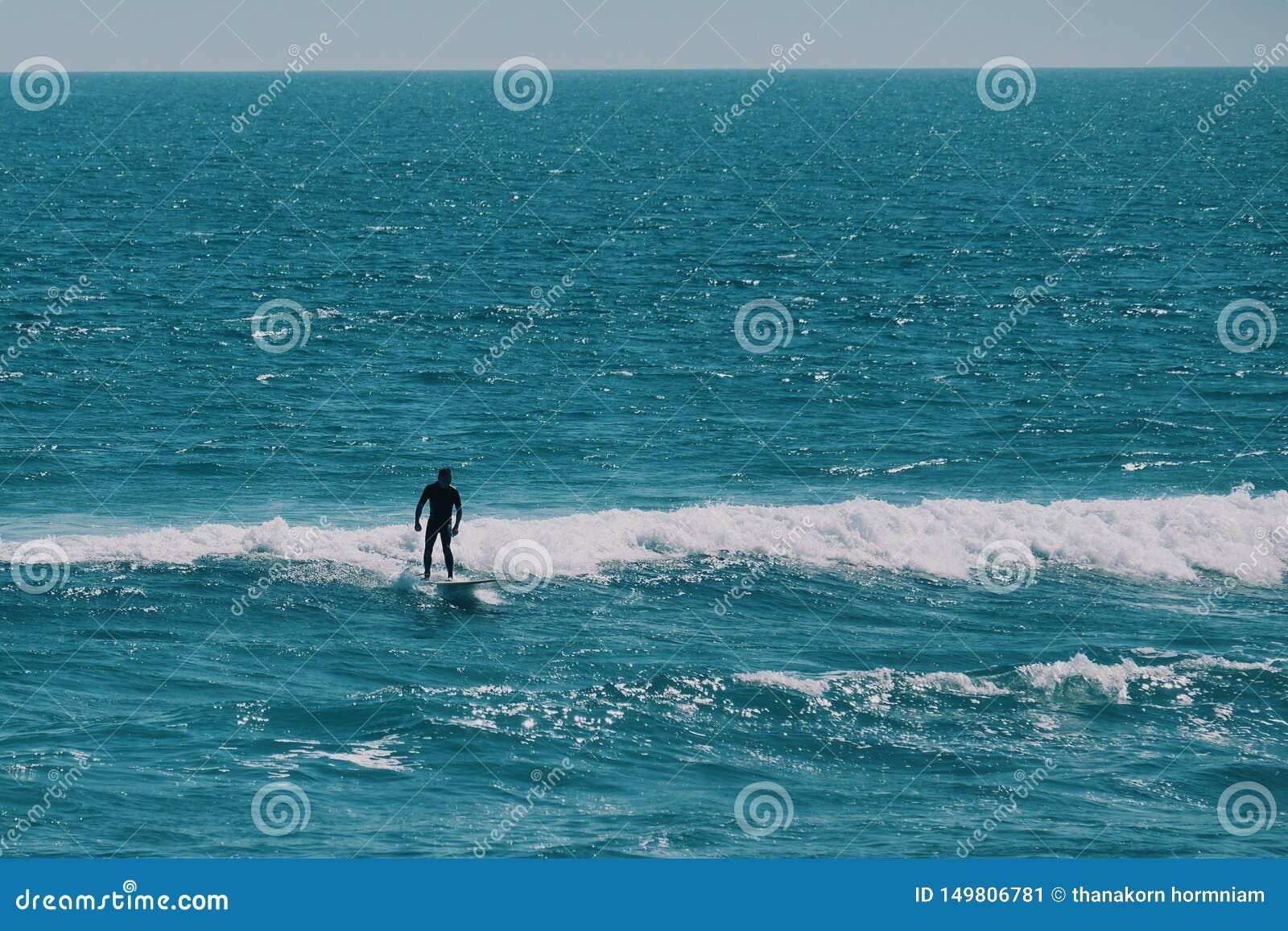 Mannelijke surfer in de oceaan, de zomer achtergrondconcept