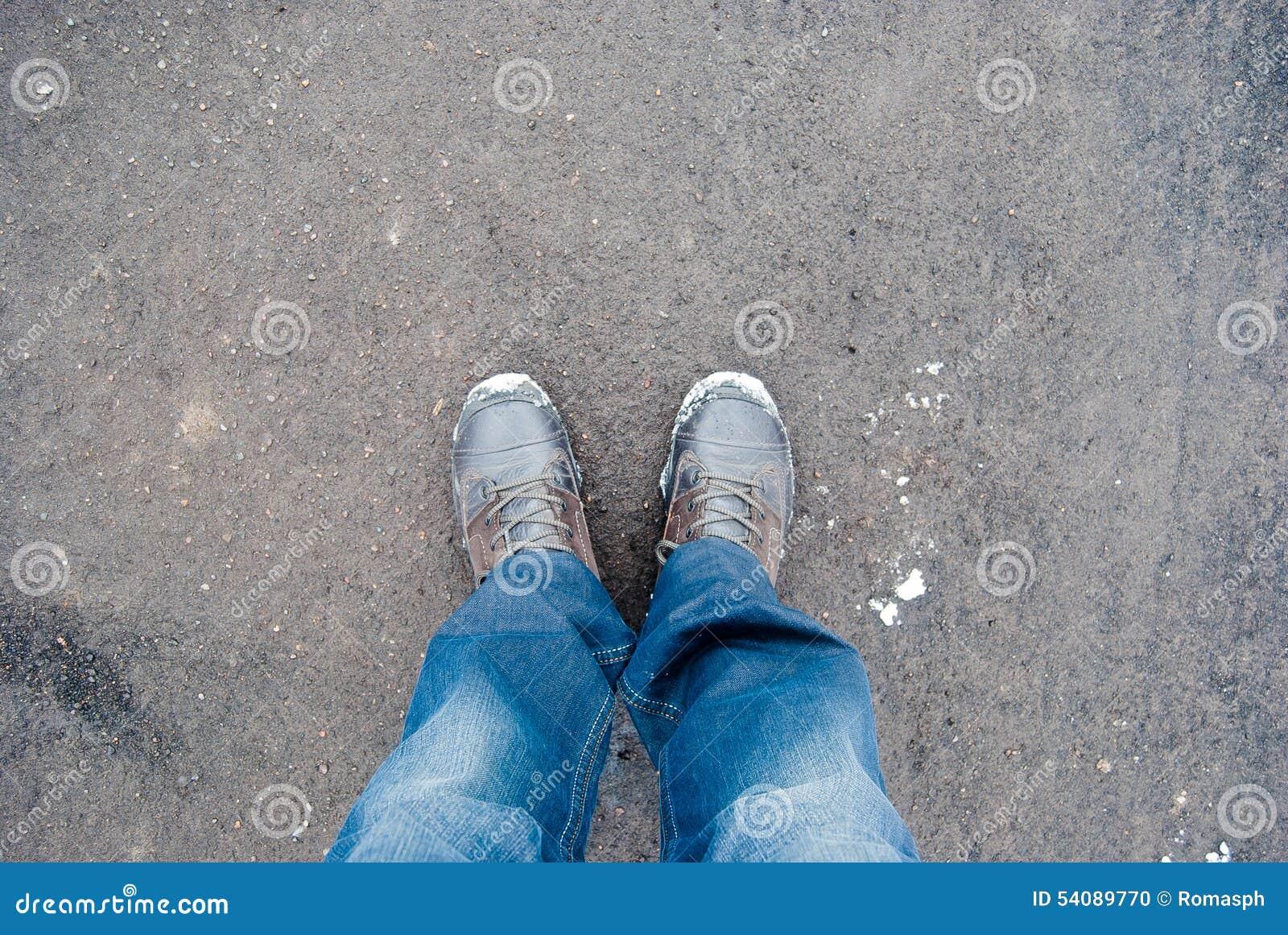 Mannelijke tennisschoenen op de asfaltweg