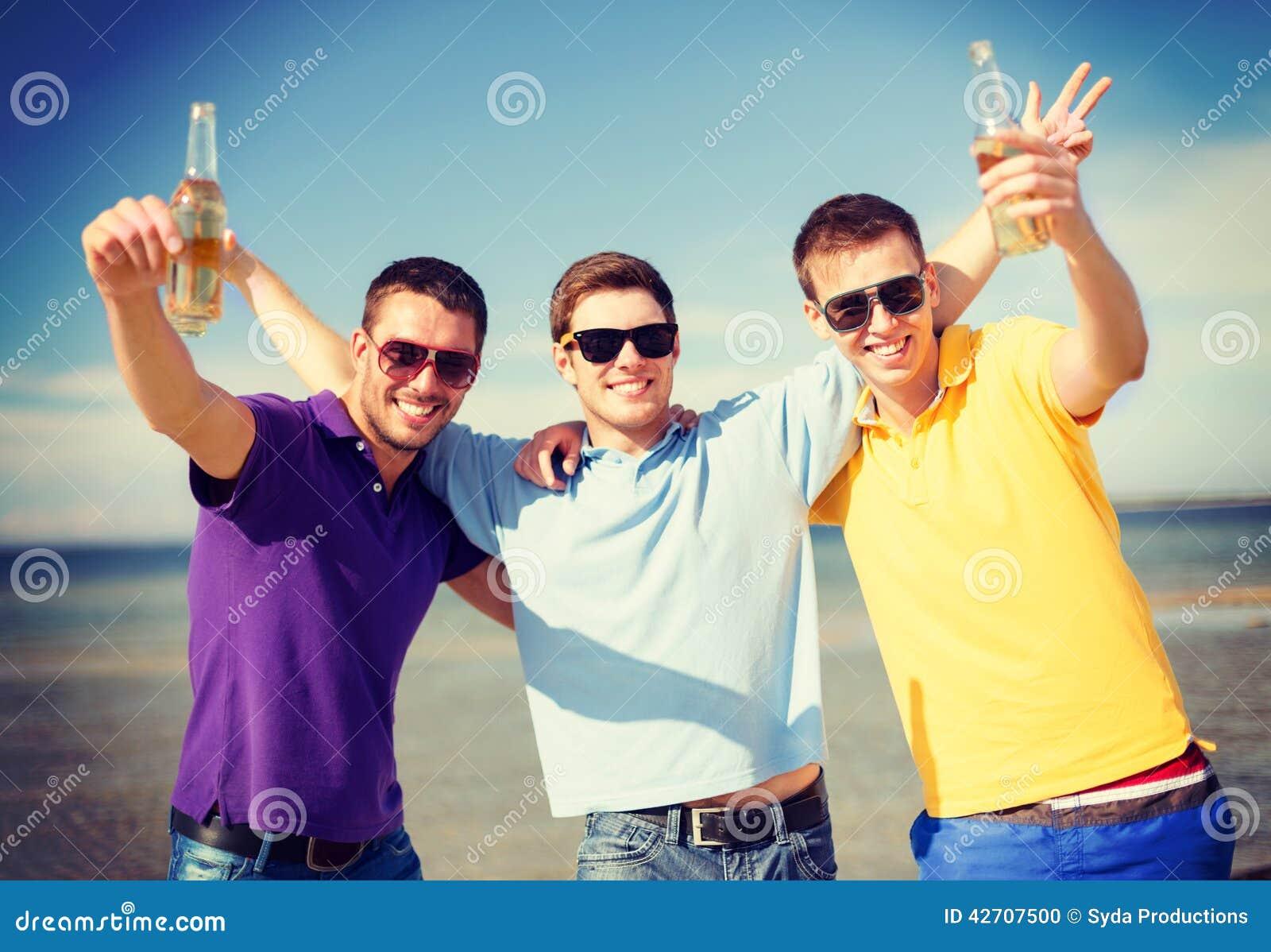 Mannelijke vrienden op het strand met flessen van drank