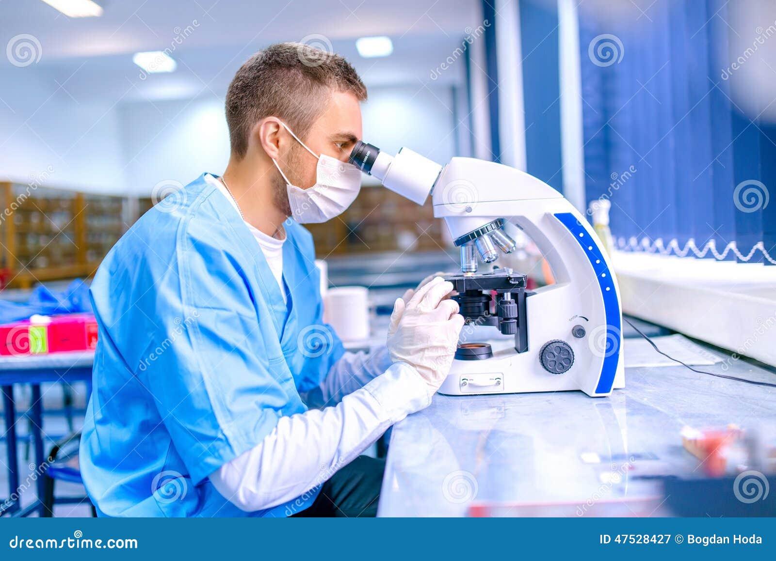 Mannelijke wetenschapper, chemicus die met microscoop in apotheek werken