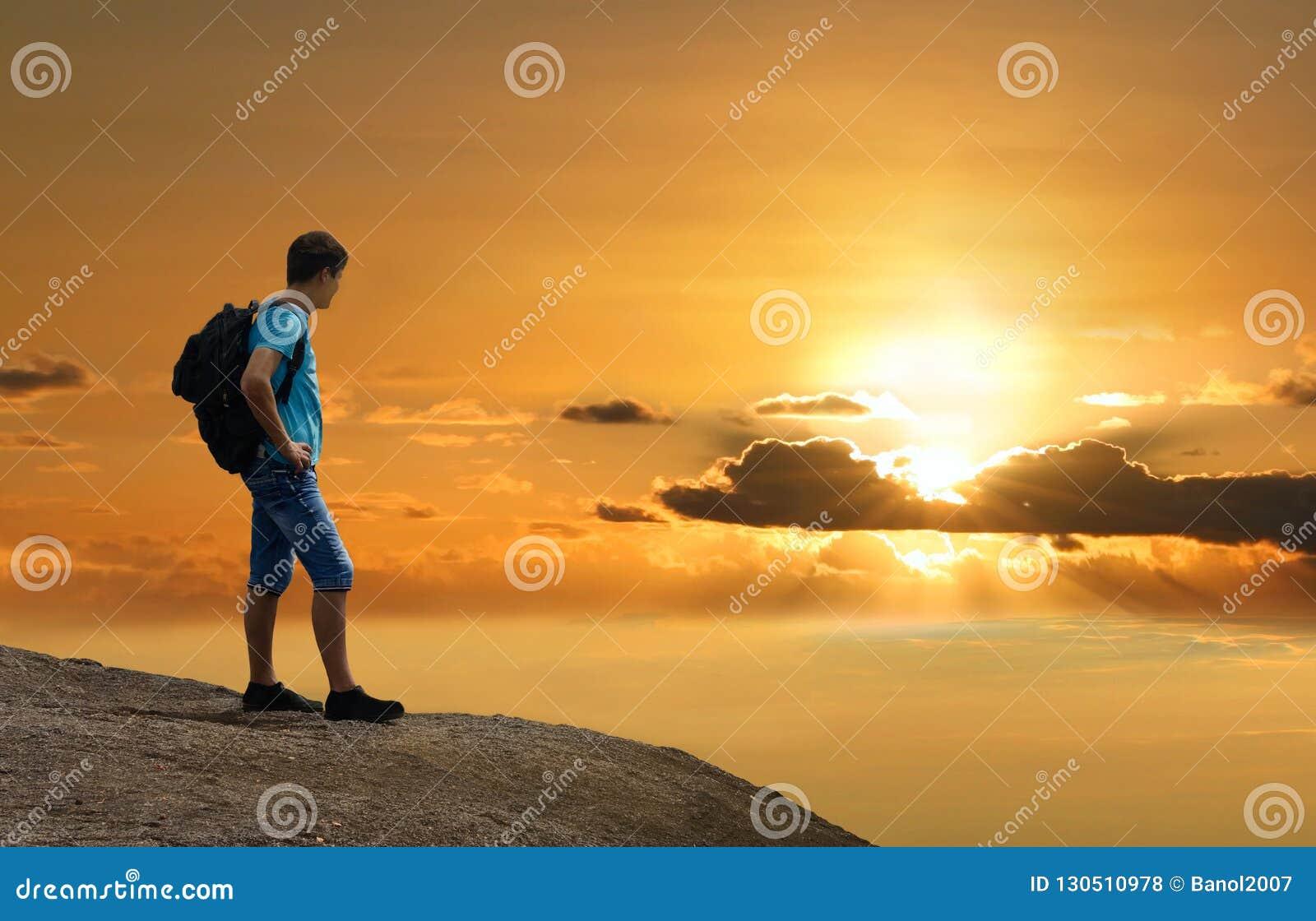 Mannen är på vaggar att tycka om solnedgång ovanför jord