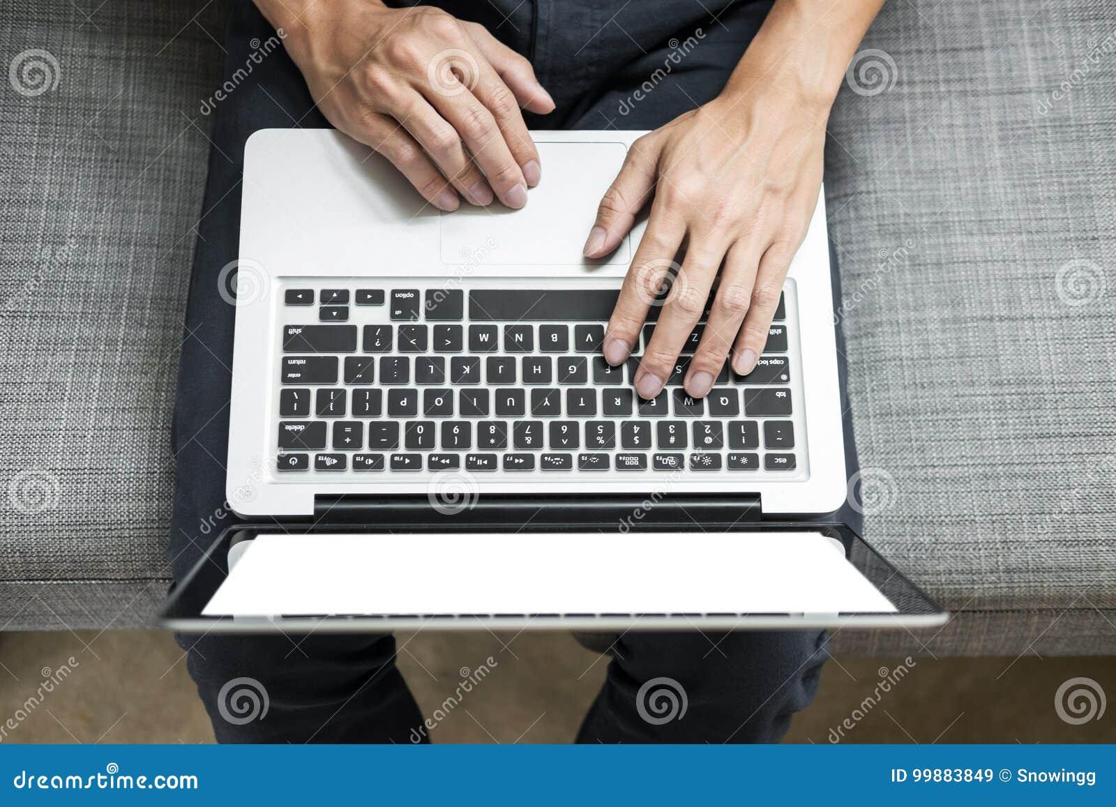 Mannen använder bärbara datorn på soffan i hans hem Sikt för hög vinkel, arbete på H
