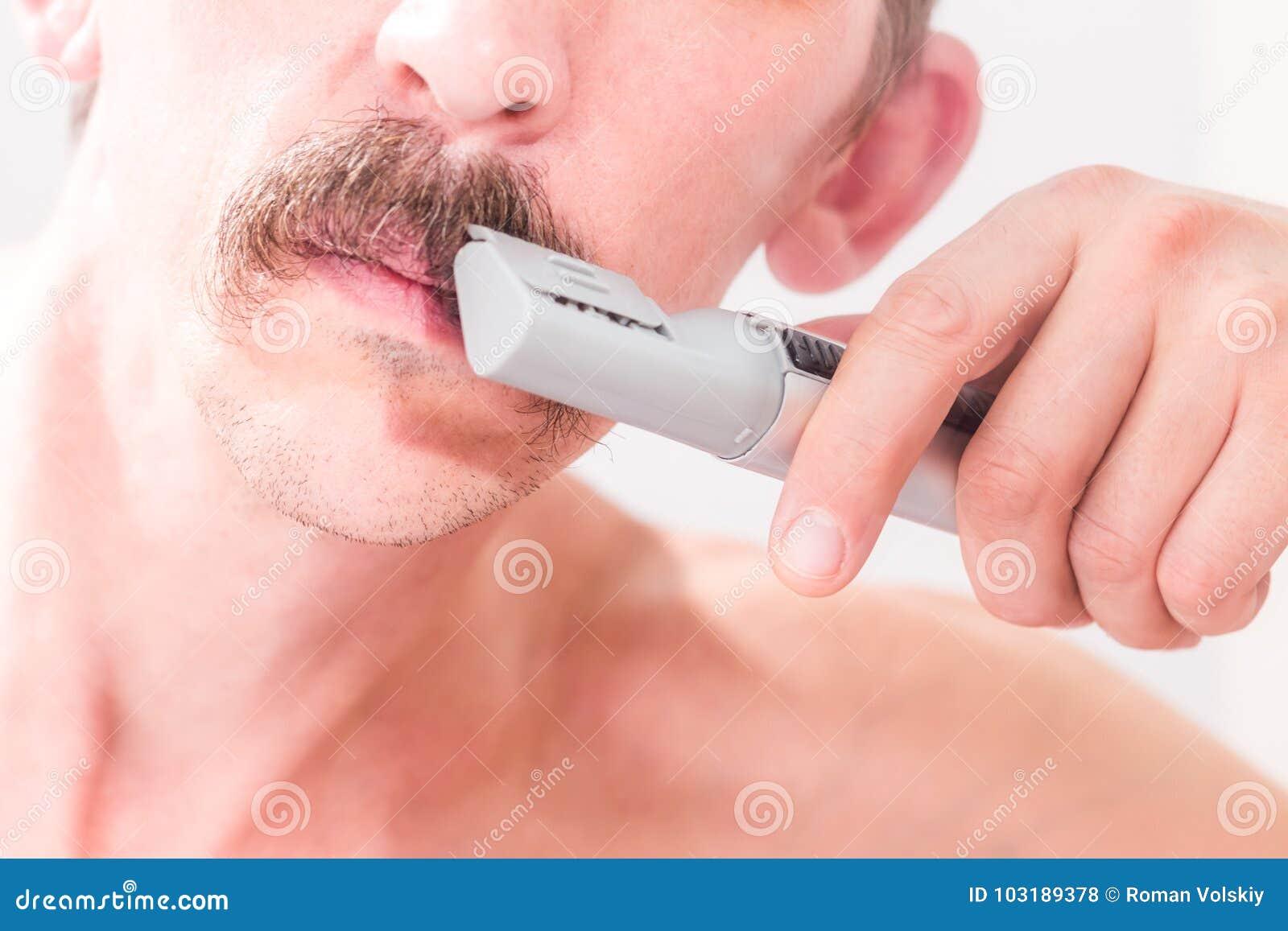 Mannen använder en beskärare för att klippa hans mustasch Närbild