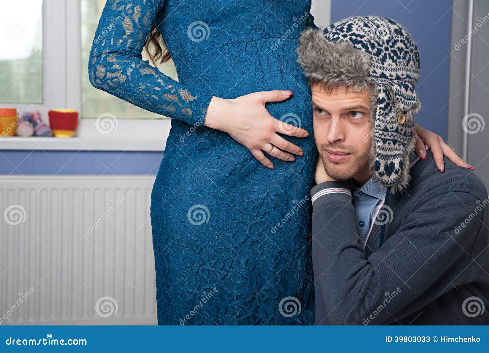 Mannen försöker att lyssna hans frus mage