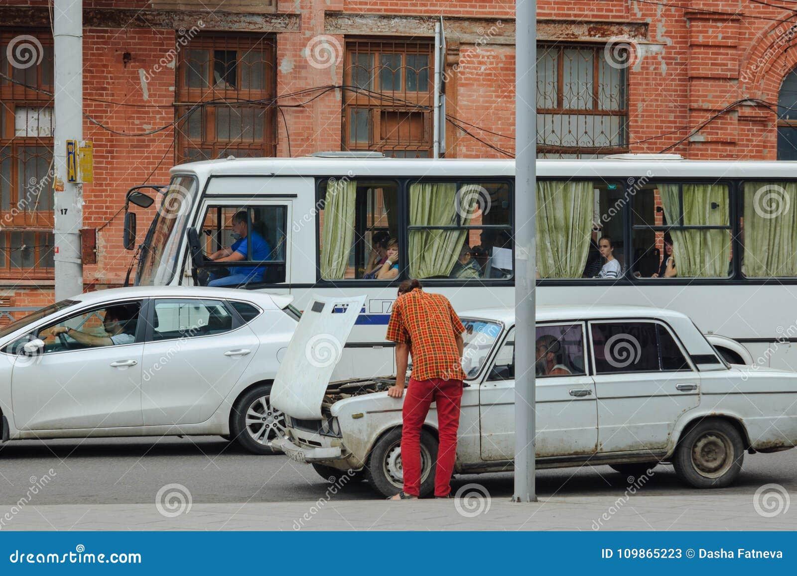 Mannen fixar bilen på gatan Verkliga livet gatahändelse