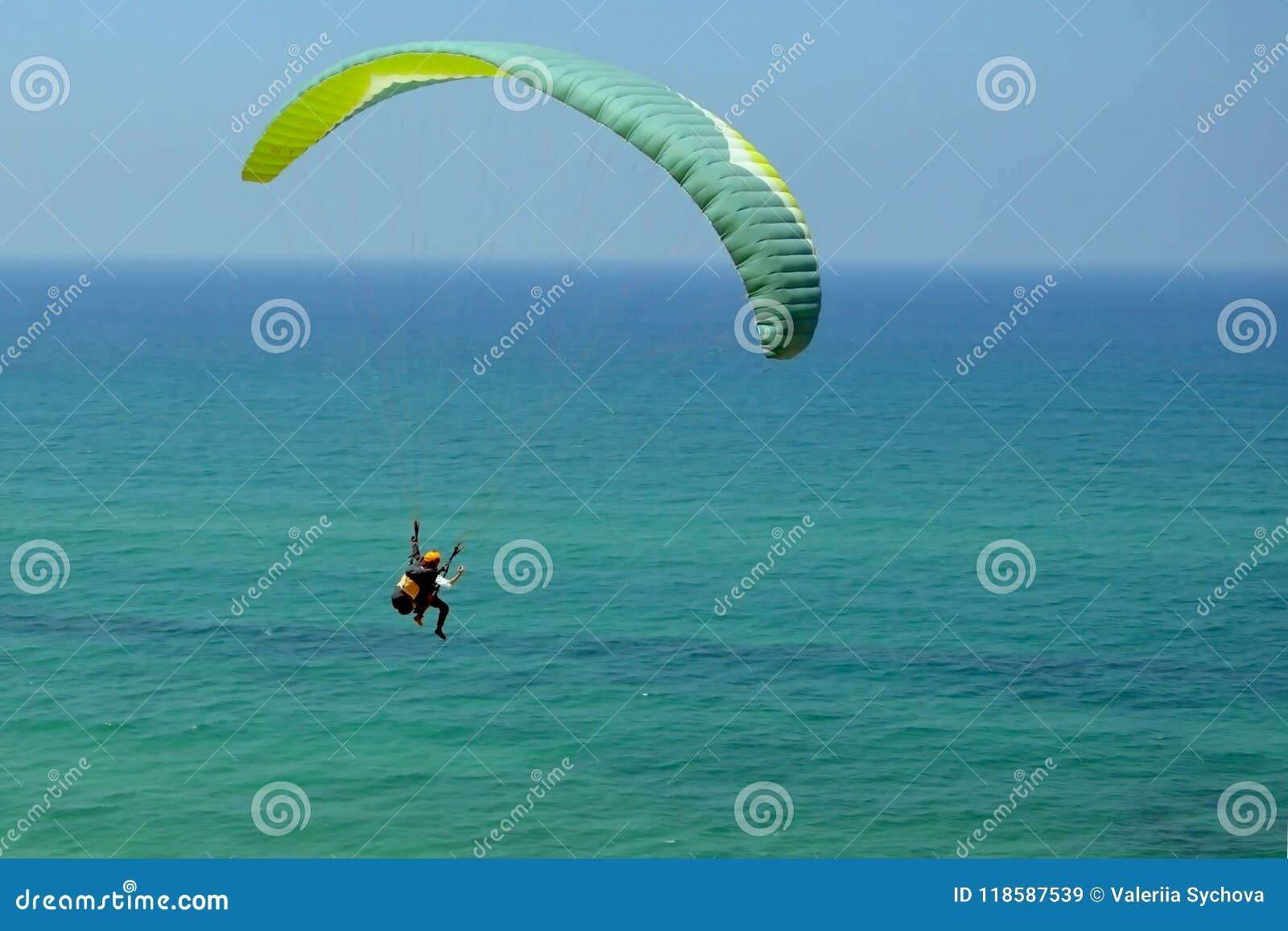 Mannen flyger på den gröna paraglideren i himlen ovanför det azura havet Jämvikt extrema sportar, livsstil Medelhav Israel