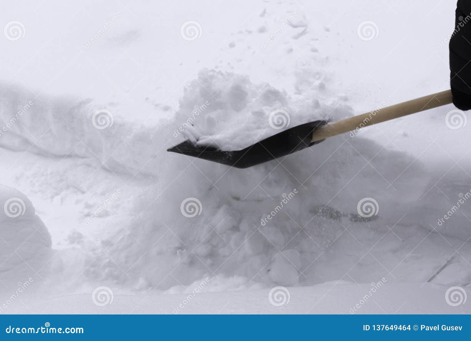 Mannen gör ren snö med en skyffel I