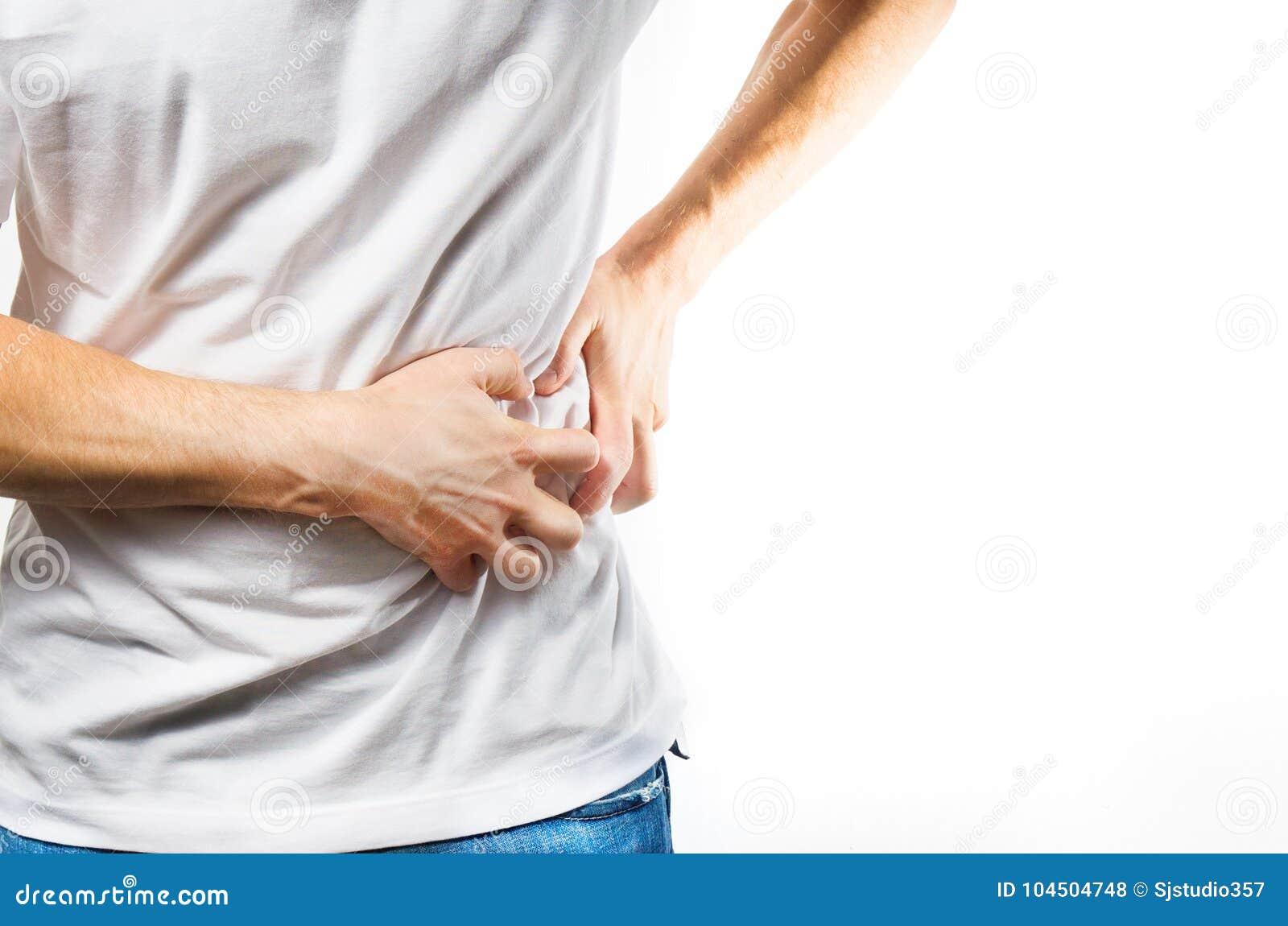 Mannen grabb i en skjorta för vit t på vita händer för en bakgrundshåll på hans mage, lever smärtar, bukspottkörteln, njureproble