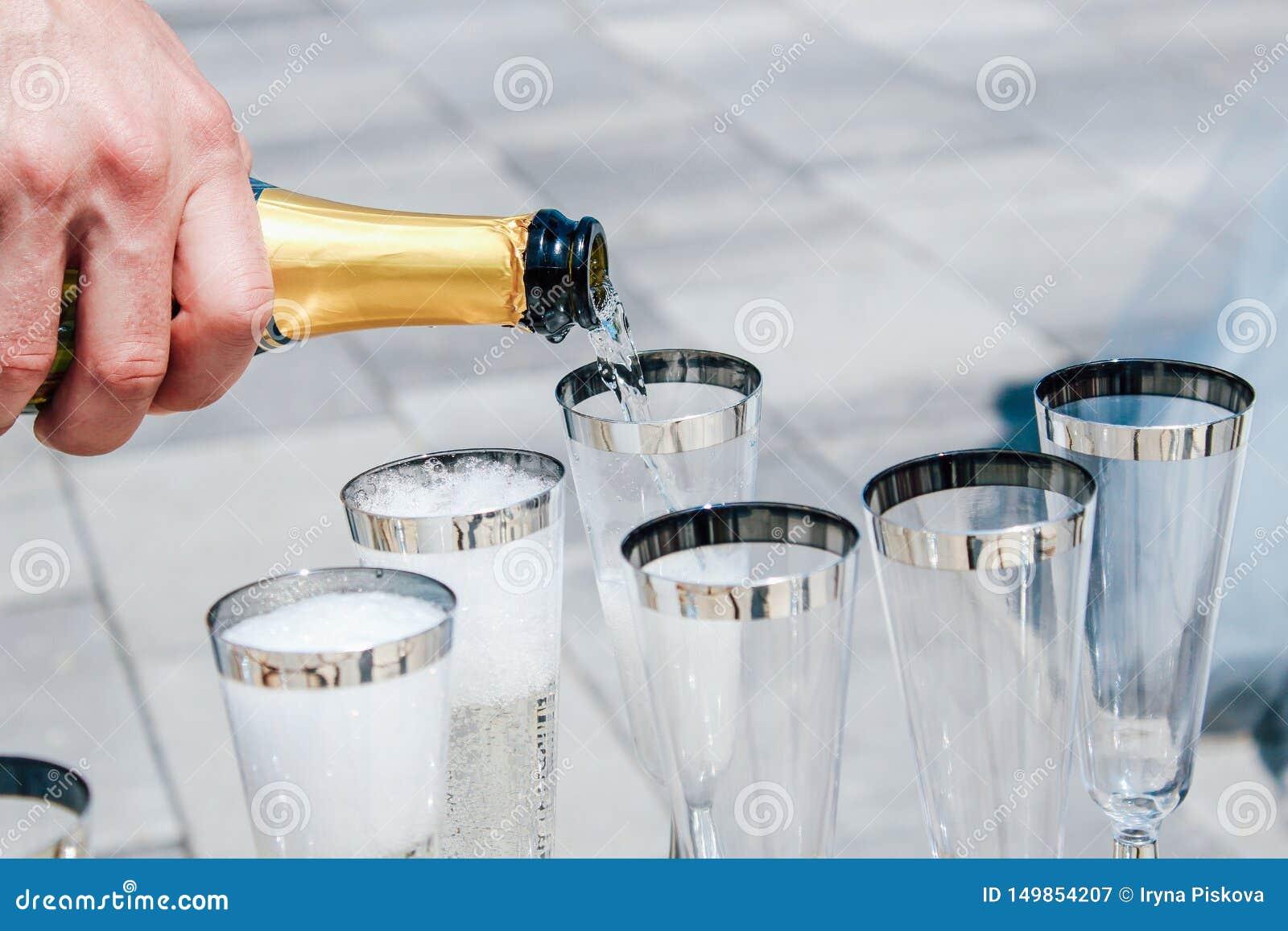 Mannen h?ller champagne in i exponeringsglas N?rbild
