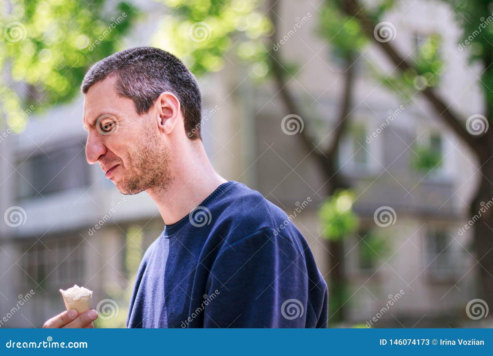 Mannen i blå pulover som äter icecream i, parkerar