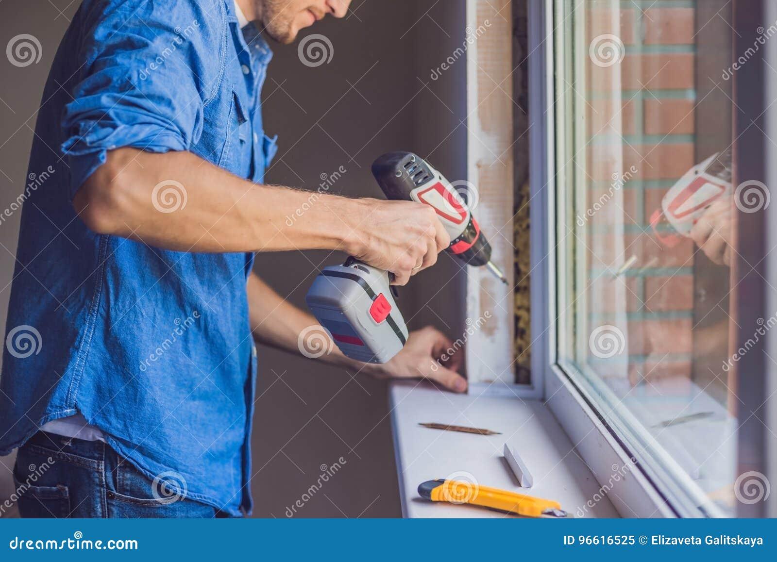 Mannen i en blå skjorta gör fönsterinstallation