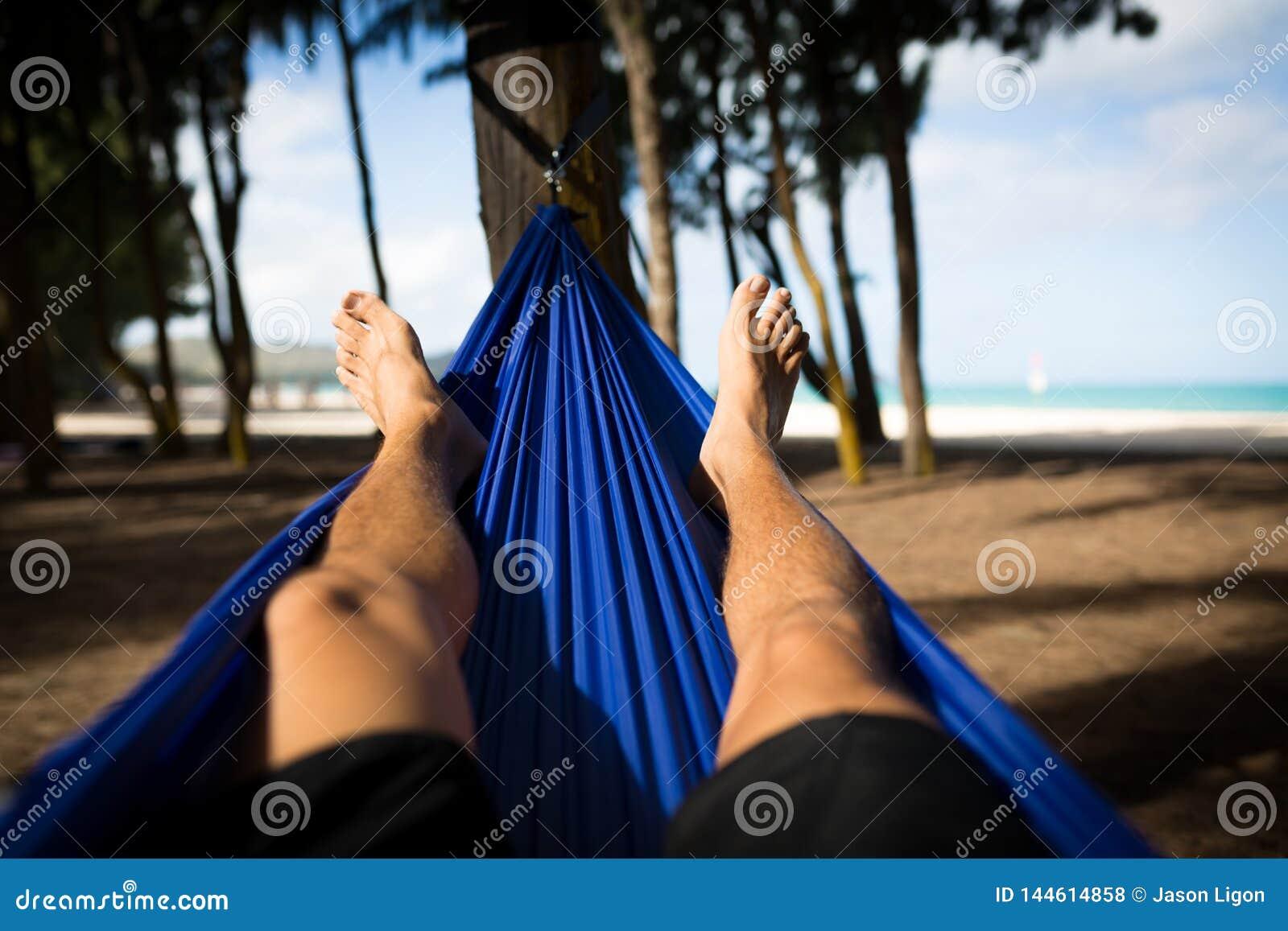 Mannen i hängmatta vänder mot stranden med lycklig fot