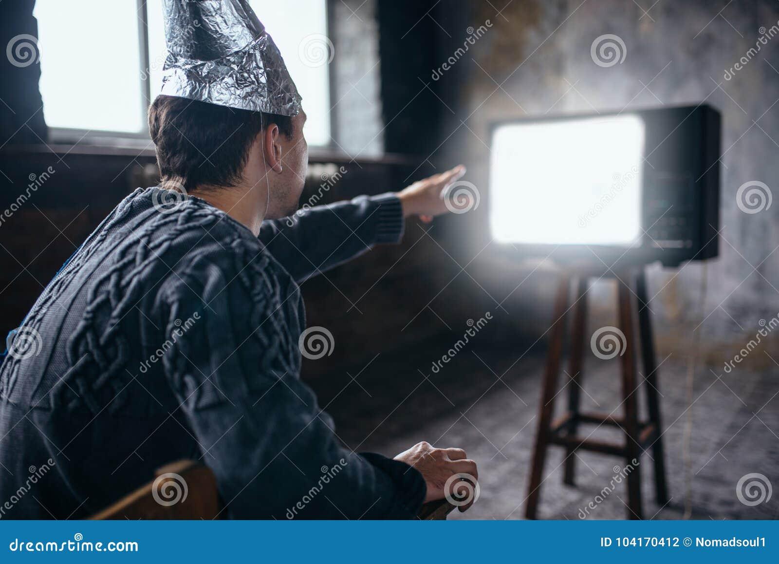 Mannen i hjälm för aluminum folie når ut till TV:N