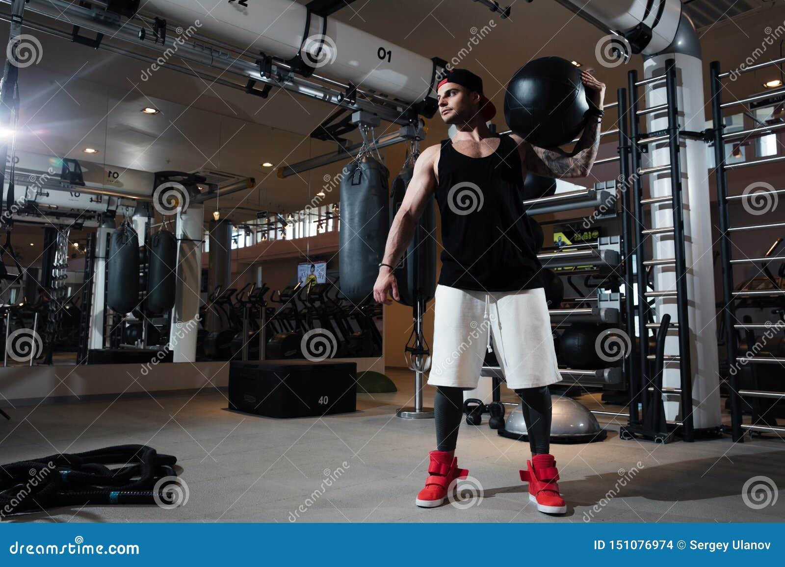 Mannen i sportswear utbildar i idrottshallen