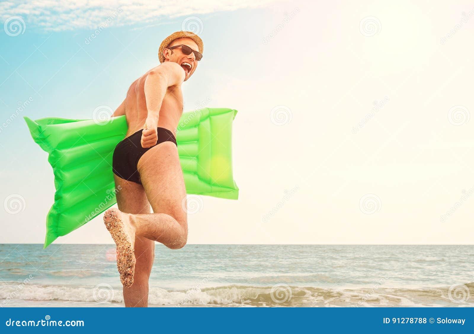 Mannen i sugrörhatt kör med luftswimimgmadrassen i havet