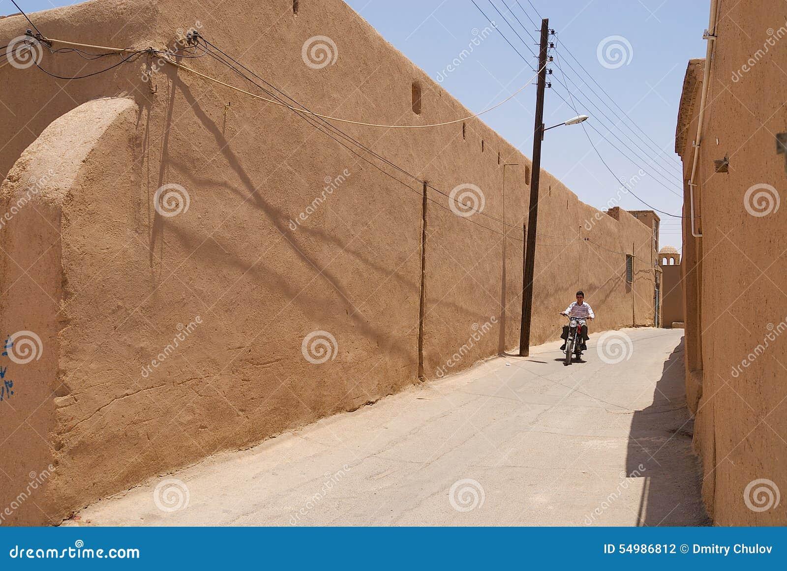 Mannen kör mopeden förbi gatan av Yazd, Iran
