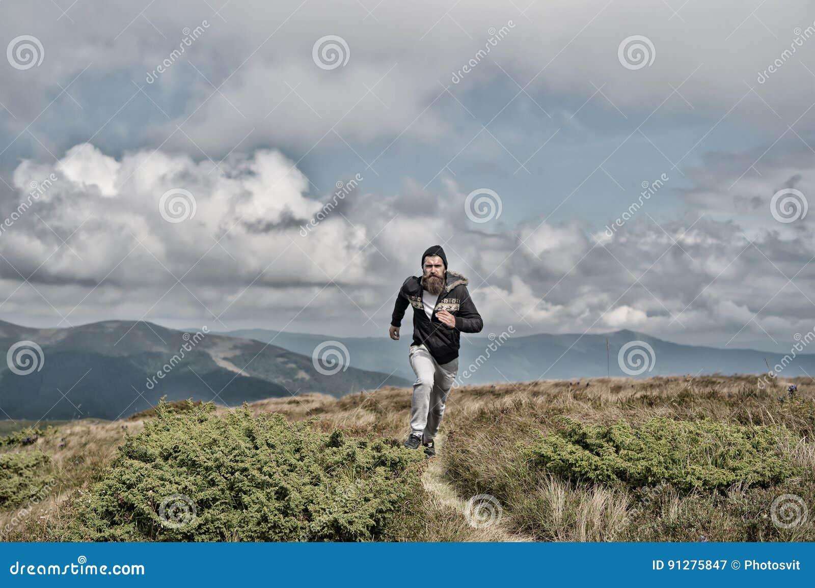 Mannen kör på grön äng i berg på molnig himmel