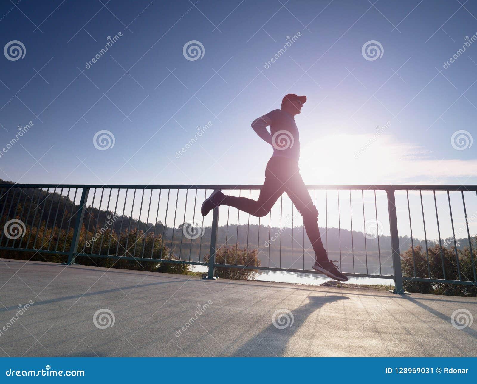 Mannen kör snabbt på kustbron Kontur av den aktiva mannen