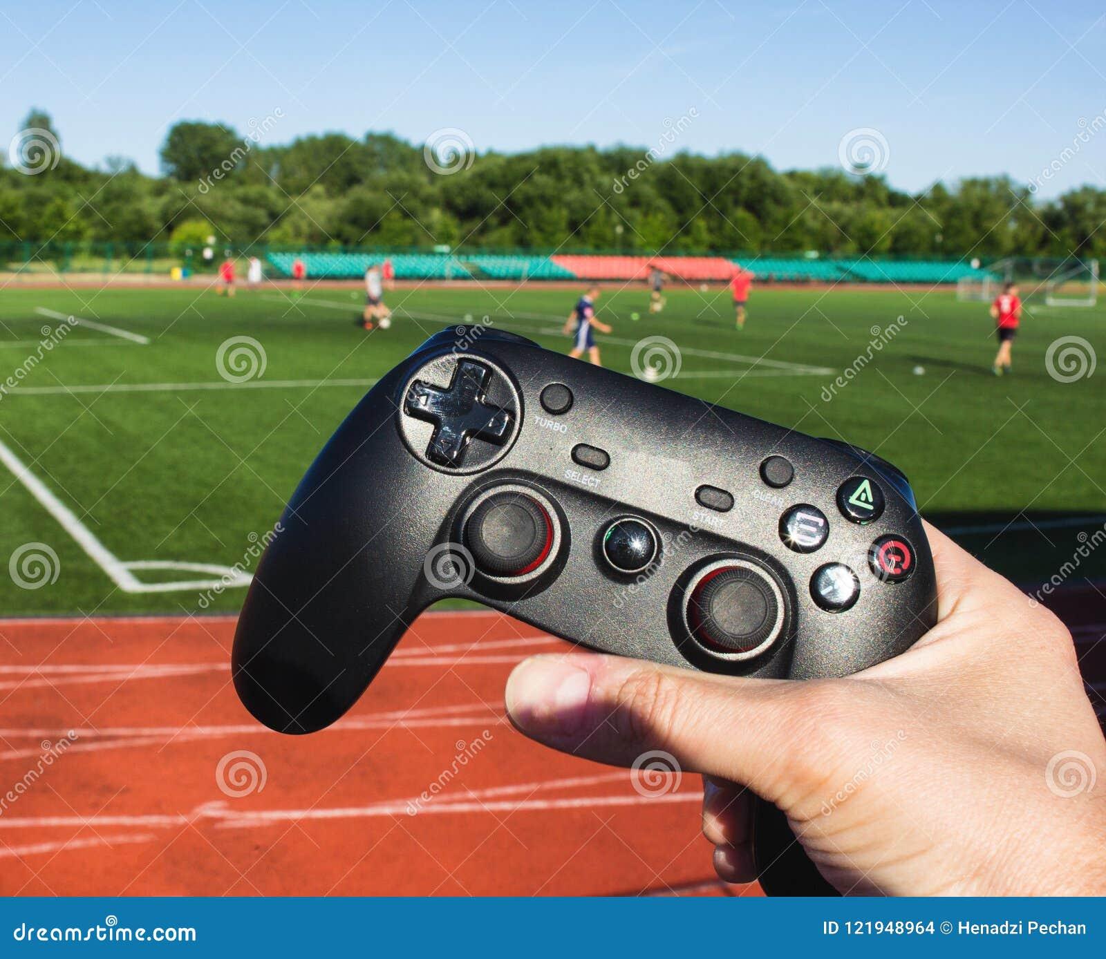 Mannen klickar på knapparna i den modiga styrspaken på bakgrunden av stadion och leken av fotboll, närbild