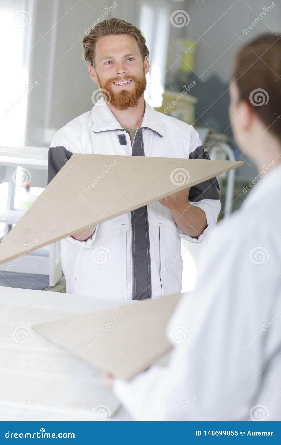 Mannen kontrollerar evennessmålarfärgapplikation
