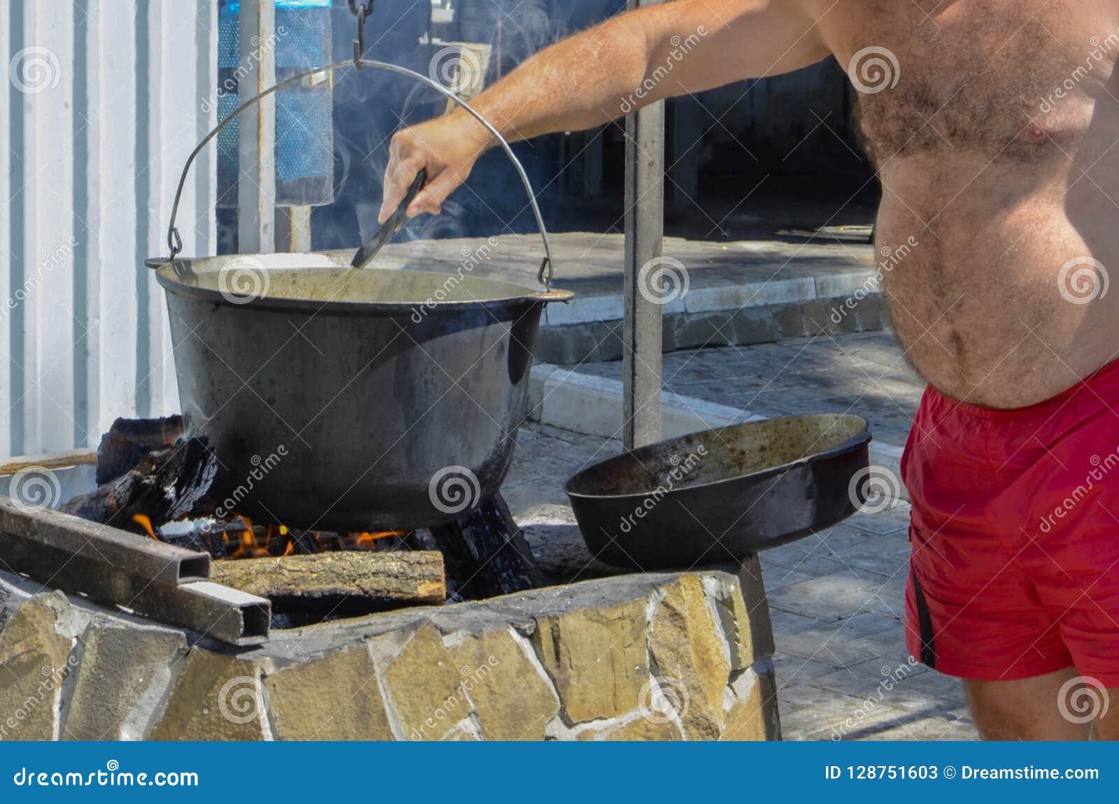Mannen lagar mat mat i natur i en kruka på en öppen brand