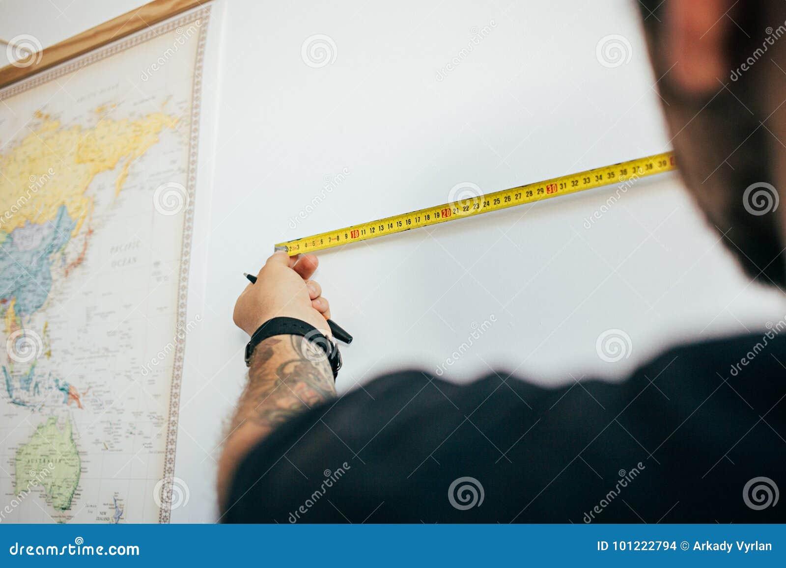 Mannen mäter väggen med att mäta bandet