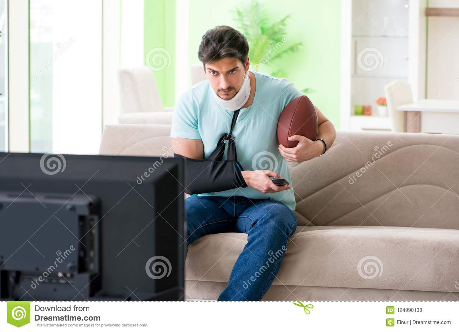 Mannen med hals- och armskada som håller ögonen på amerikansk fotboll på tv