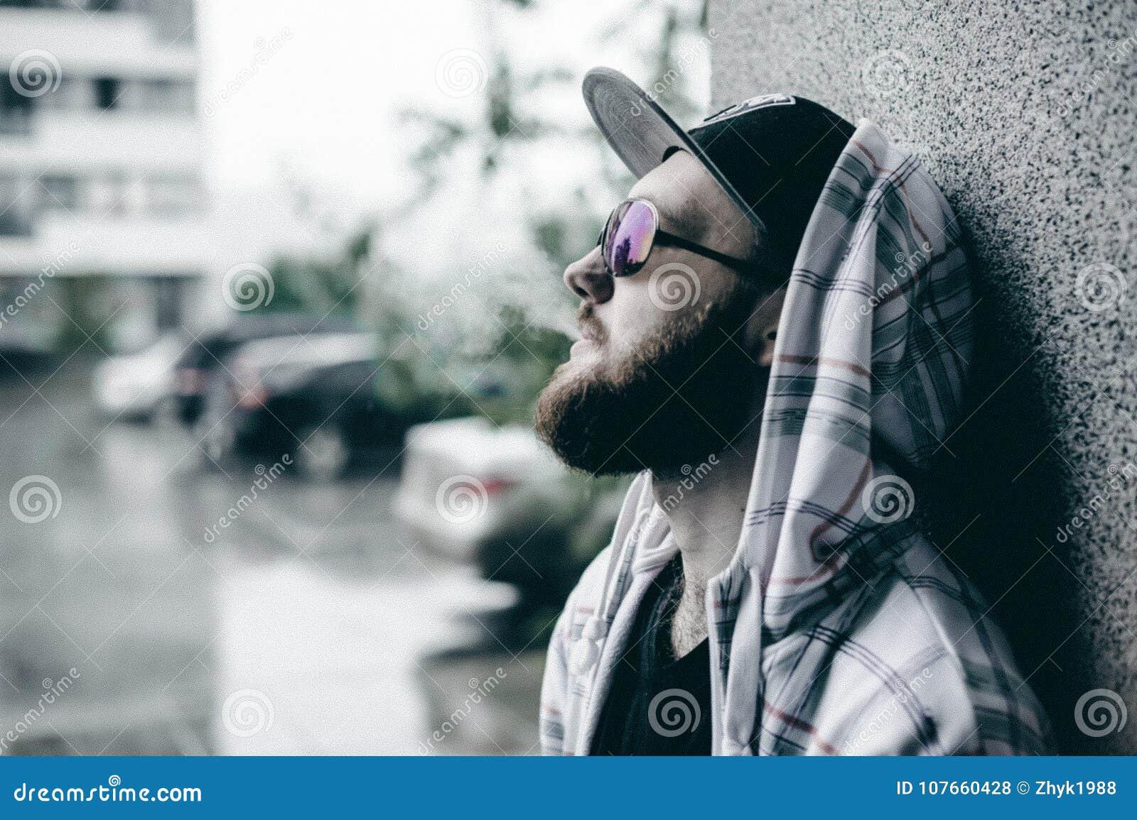 Mannen med skägget i ljust rutigt omslag med huven i ett lock och solglasögon som fritt går runt om stad, röker encigarett