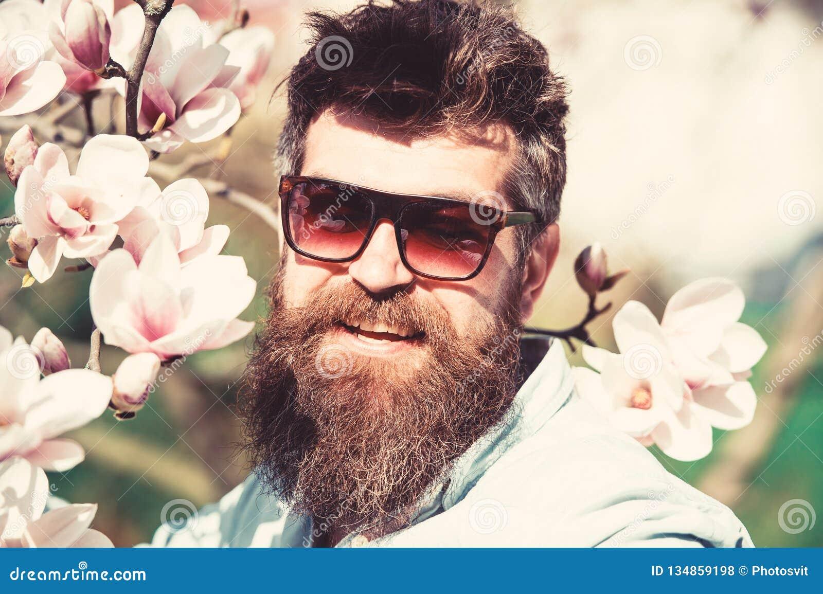 Mannen med skägget och mustaschen bär solglasögon på solig dag, magnoliablommor på bakgrund för begreppsframsida för skönhet blå