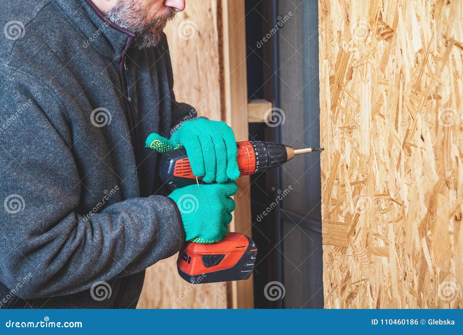 Mannen med skägget vrider skruven med hjälpmedlet