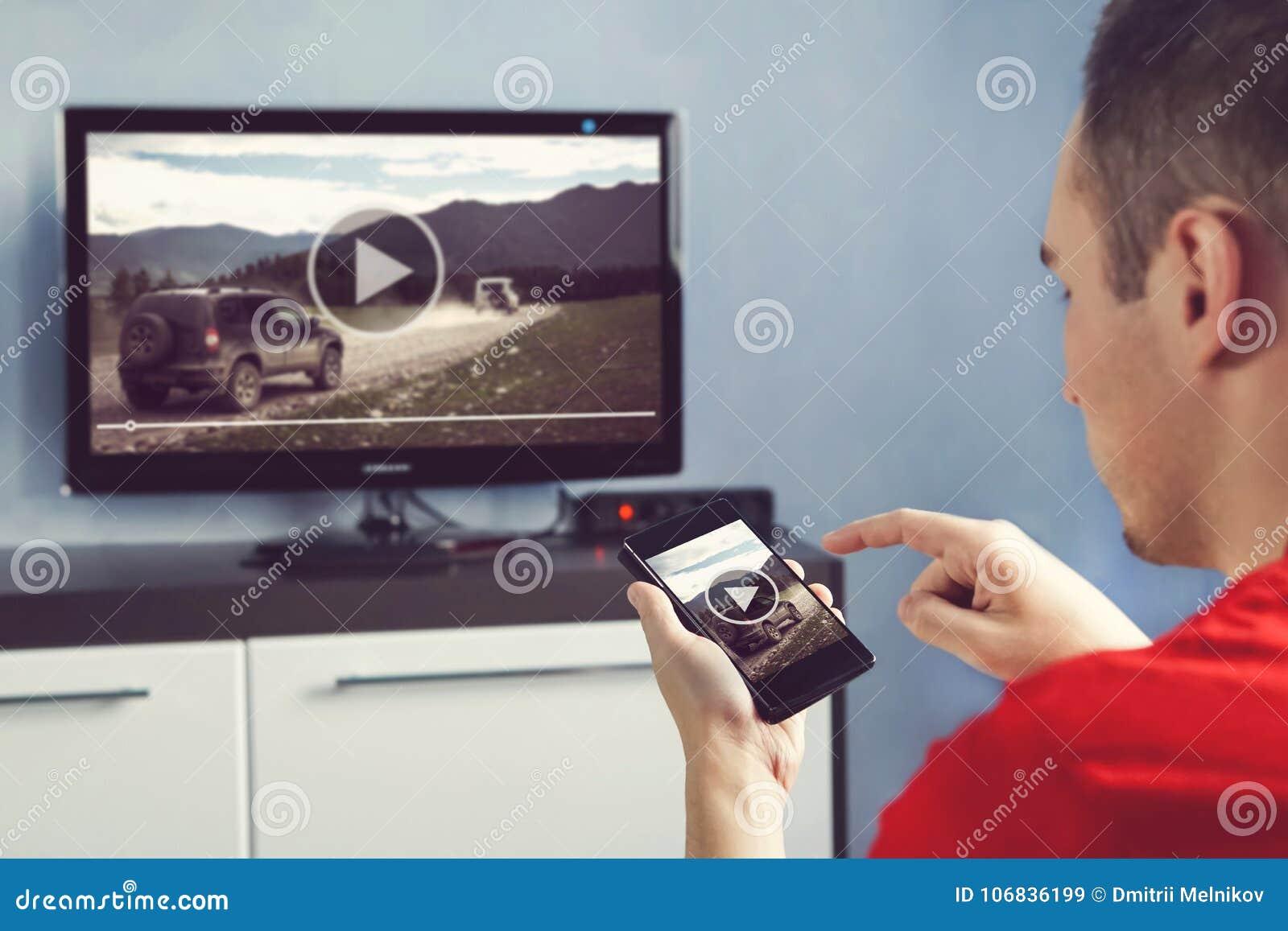 Mannen med Smartphone förband till en TV som håller ögonen på videopn hemmastatt