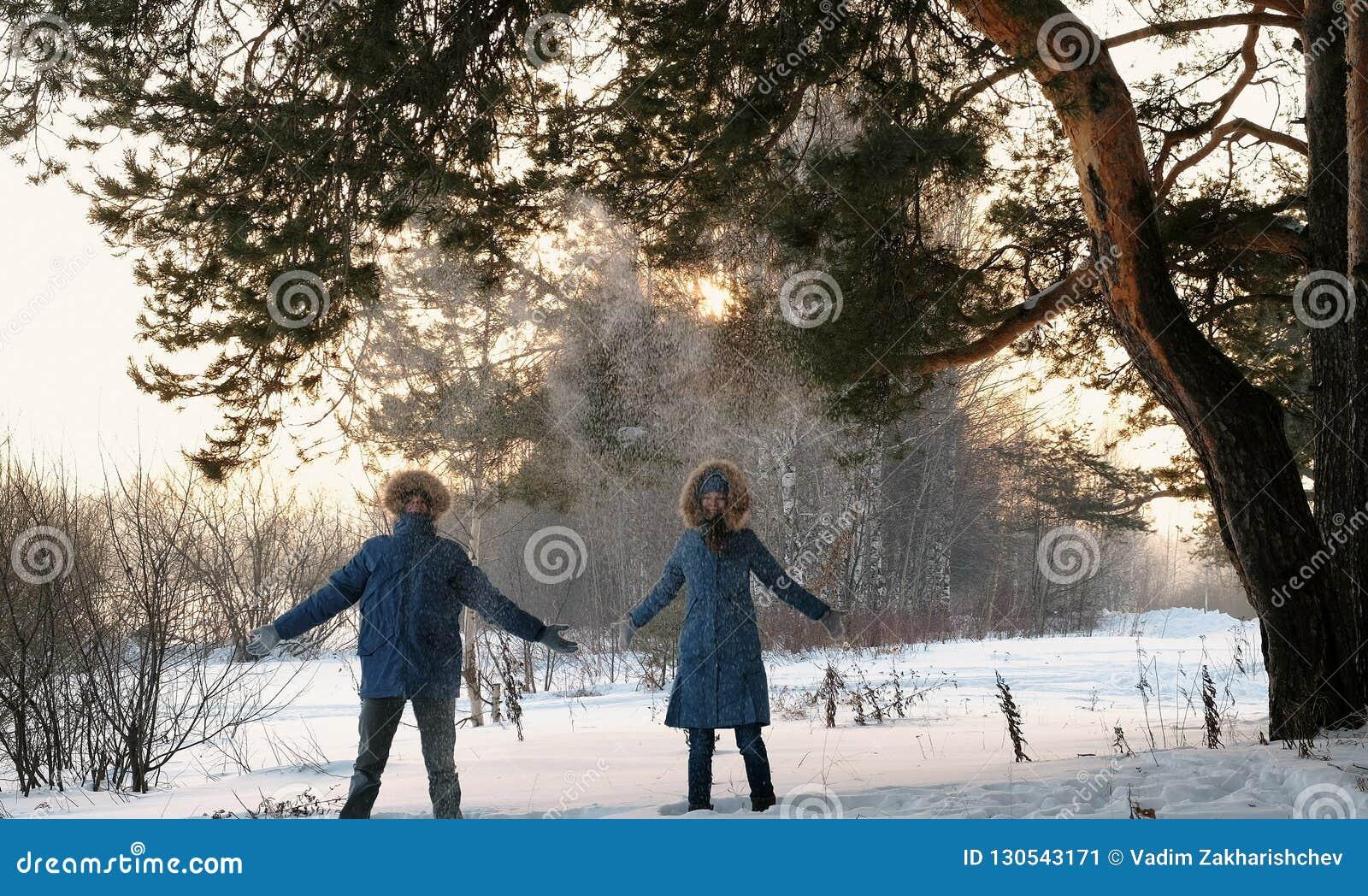 Mannen och en kvinna i blåa omslag kastar ner snö upp i det vinterskogen och leendet Bekläda beskådar