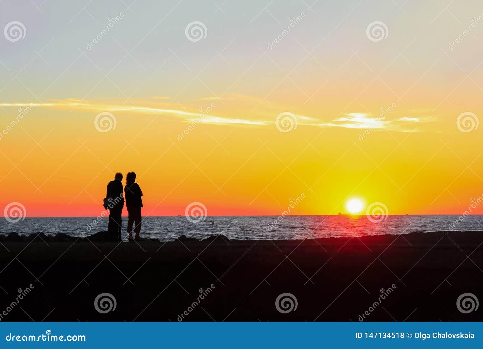 Mannen och kvinnan beundrar den färgrika solnedgången på stranden