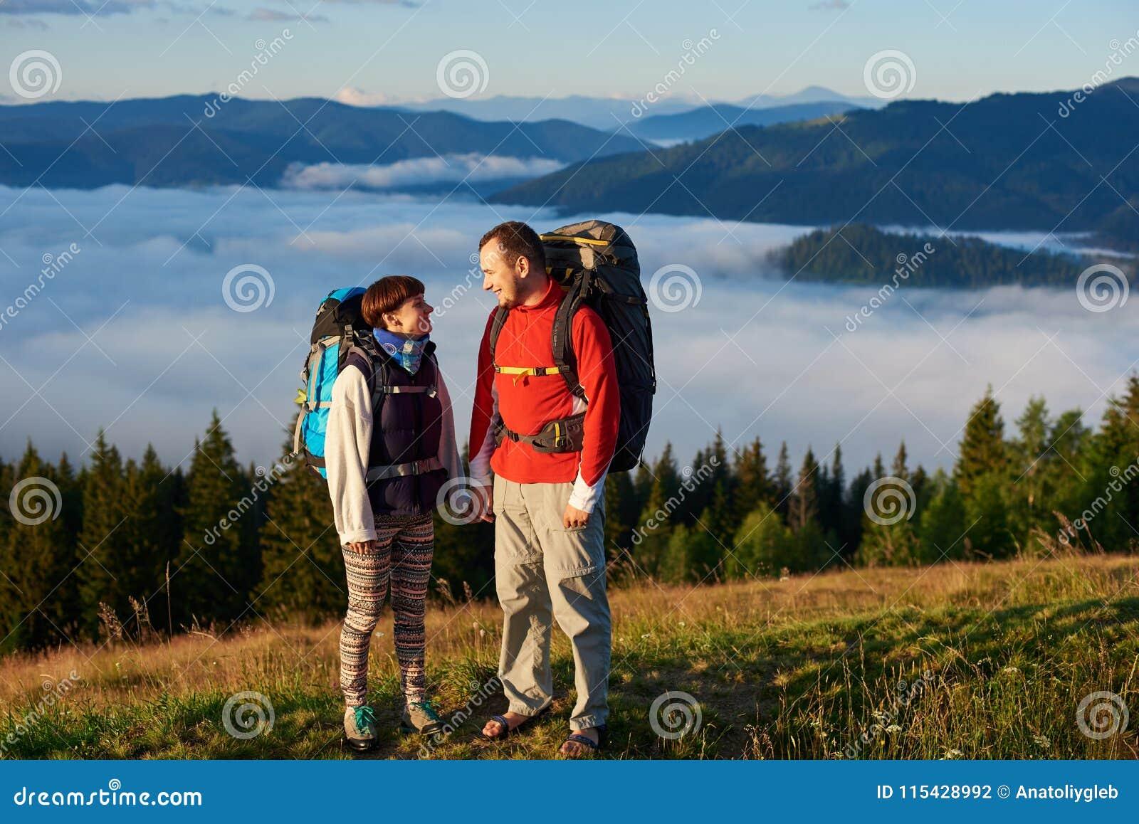 Mannen och kvinnan med ryggsäckar ser de i strålar av solnedgången mot berg