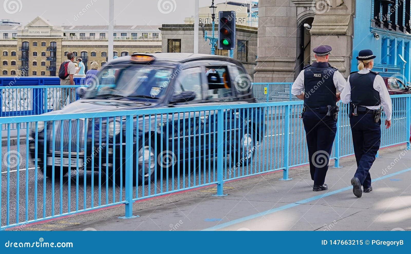 Mannen och kvinnliga Bobbies patrullerar tornbron