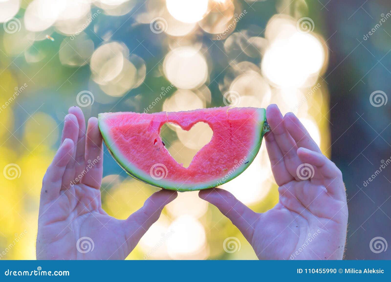 Mannen räcker den hållande vattenmelonskivan med hjärtaform i natur