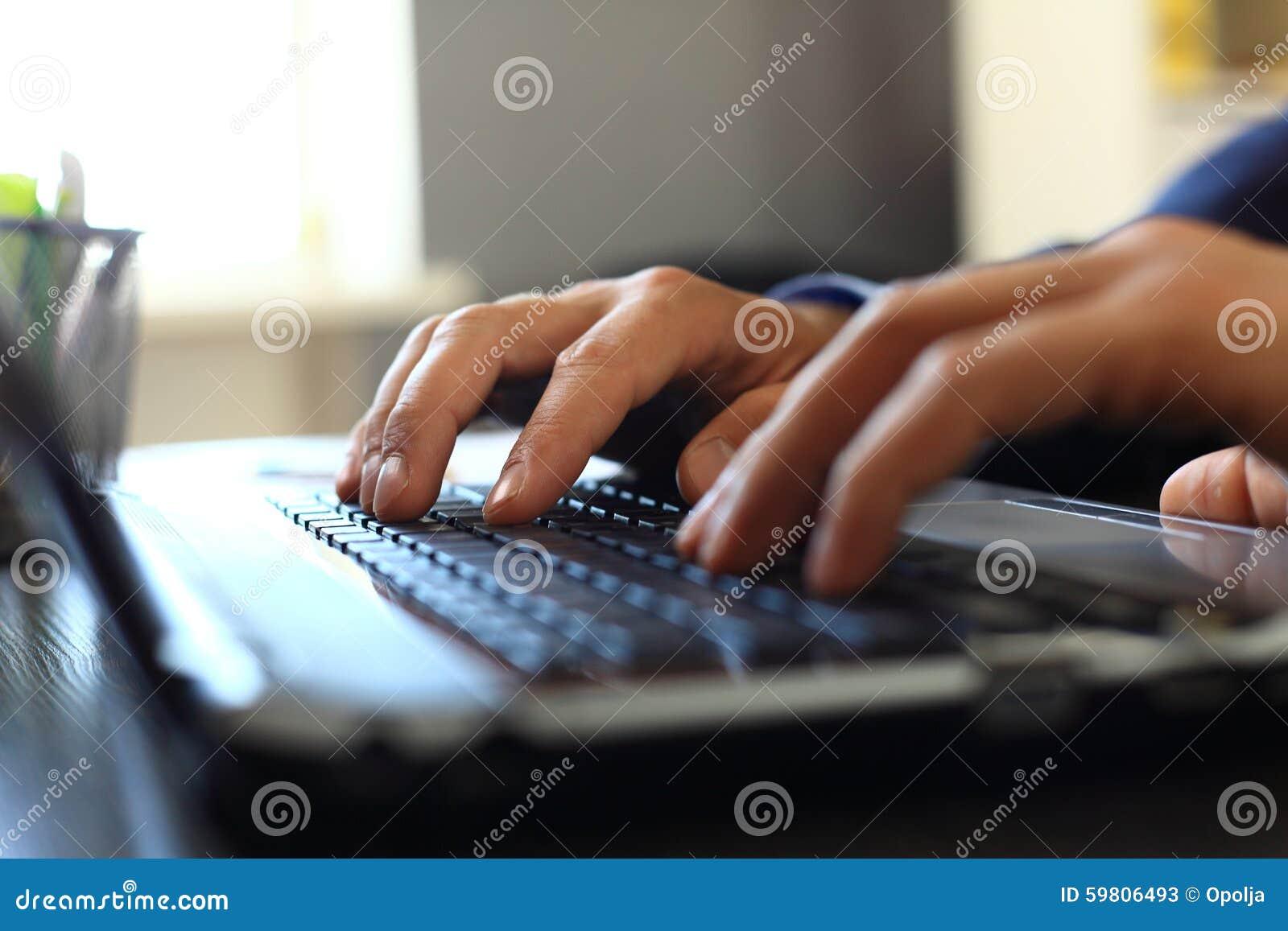 Mannen räcker maskinskrivning på bärbar datortangentbordet