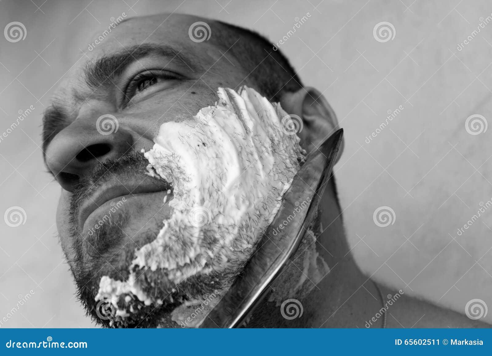 Mannen rakar hans skägg med en kniv