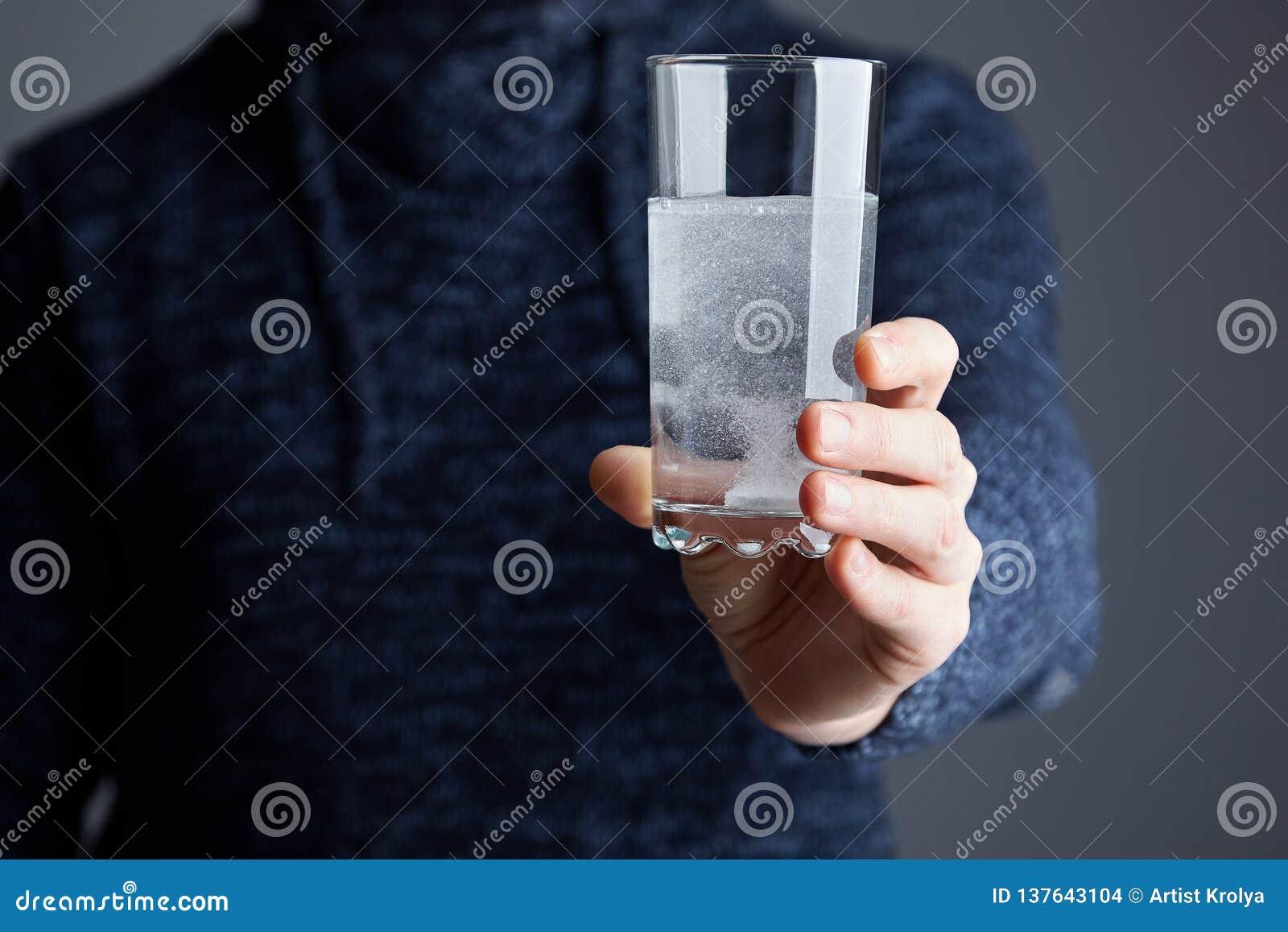 Mannen rymmer exponeringsglas av vatten med det upplösta pillret