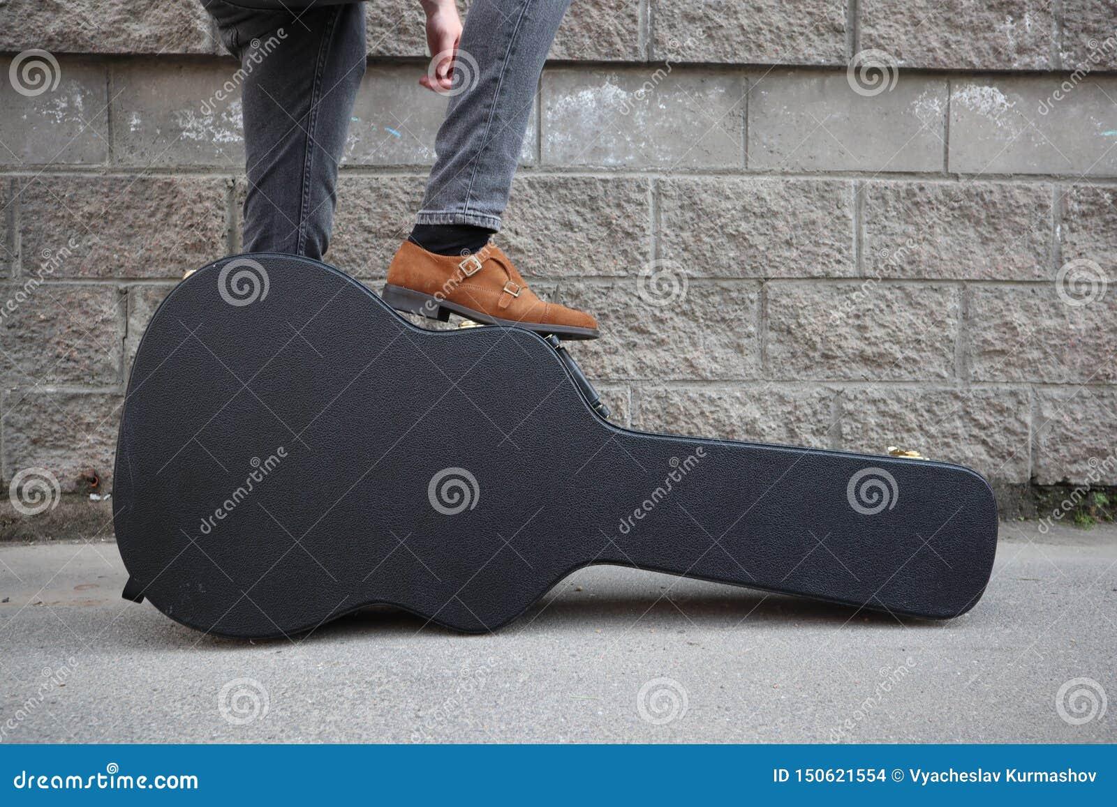 Mannen satte hans fot på ett hårt gitarrfall H?rt fall f?r elektrisk gitarr Iklädd jeans för man som rymmer gitarrfallet mot vägg