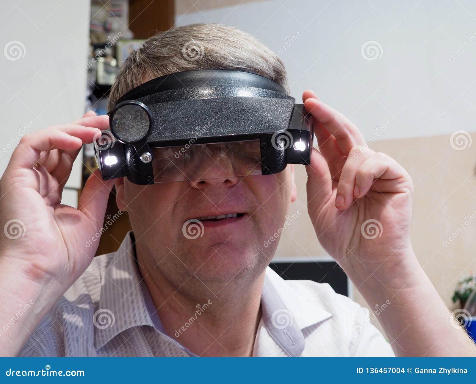 Mannen ser in i den optiska apparaten