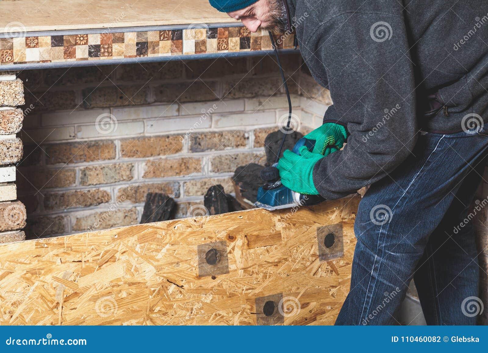 Mannen skrapar den wood plattan med elkraftnivån