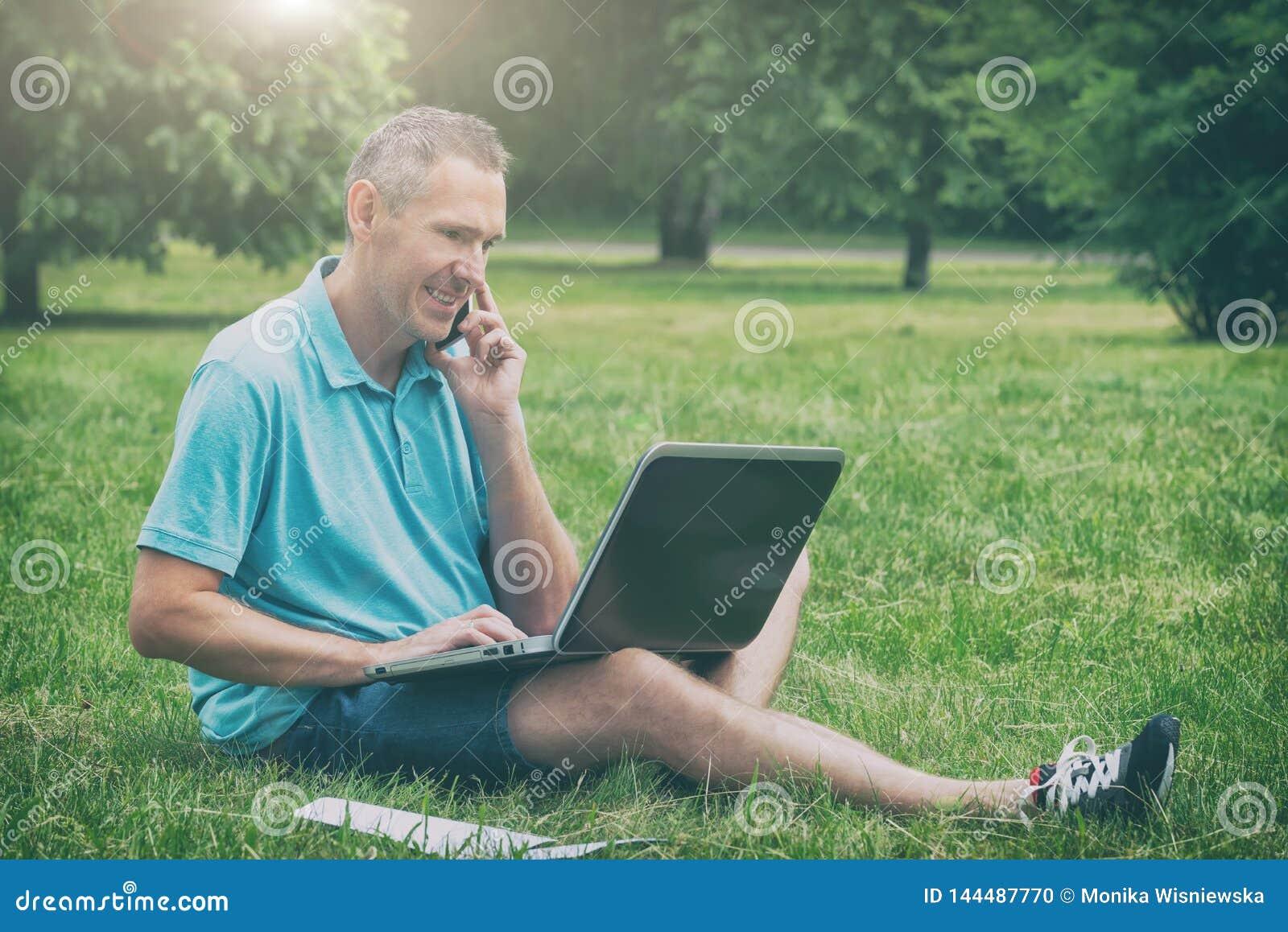 Mannen som arbetar med hans bärbar dator i, parkerar