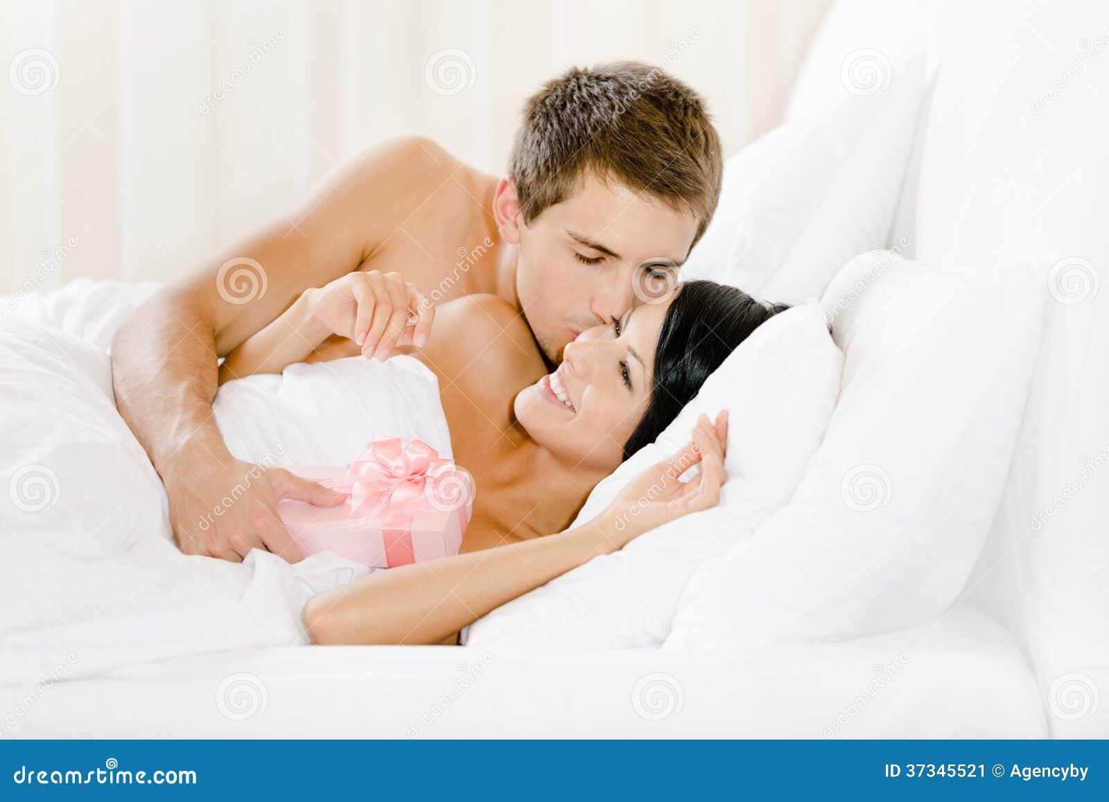 Mannen som ligger i säng, ger gåva till damen