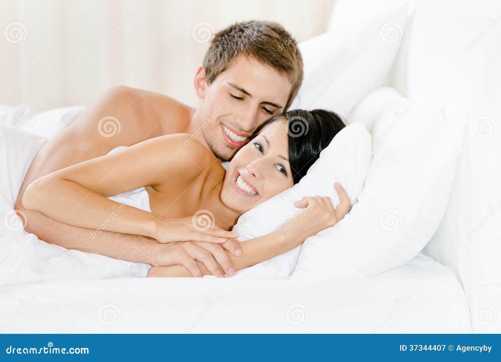 Mannen som ligger i sovrum, omfamnar kvinnan