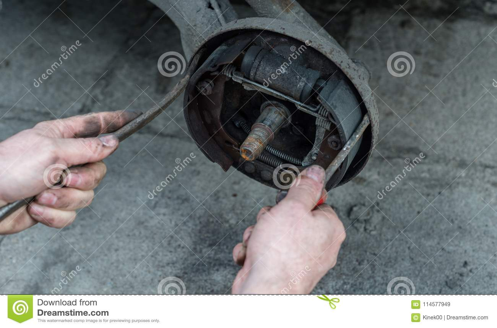 Mannen som reparerar bromstrummor för bil och kontroller bromsblocken genom att använda två skruvmejslar