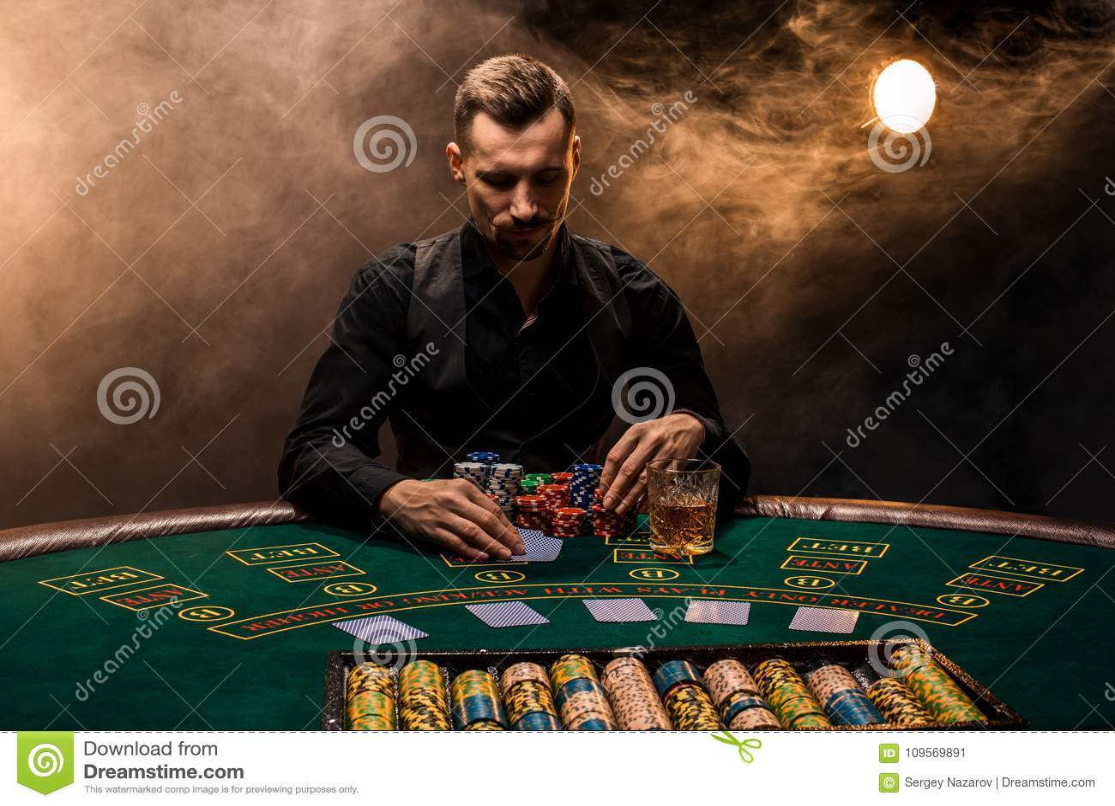 Mannen spelar poker med en cigarr och en whisky En man som segrar alla chiper på tabellen med tjock cigarettrök