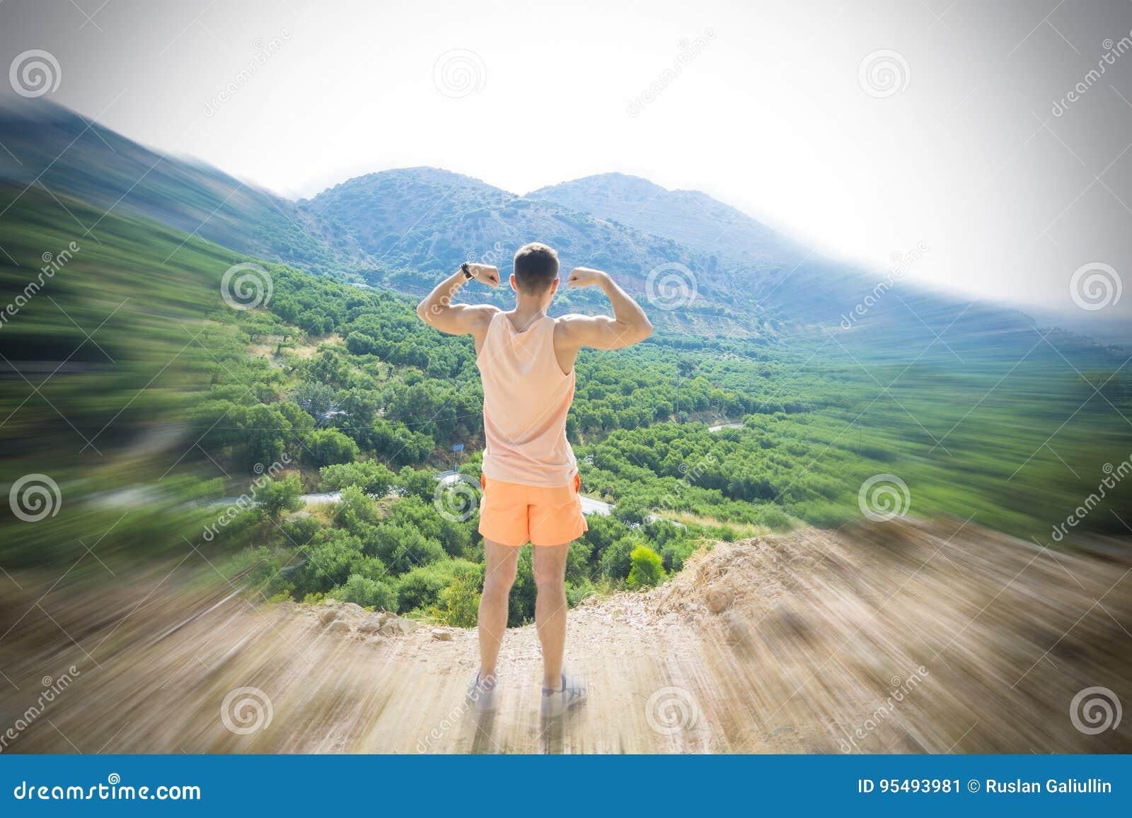 Mannen står i vinnare poserar på överkanten av ett berg Begreppet av ledarskap, styrka, förtroende och frihet
