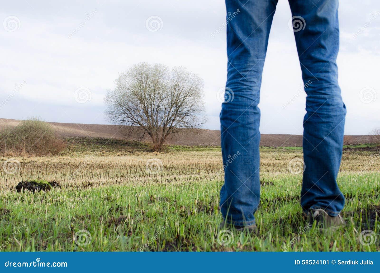 Mannen står på bränt fält med några rest av grönt gräs och det ensamma trädet på det